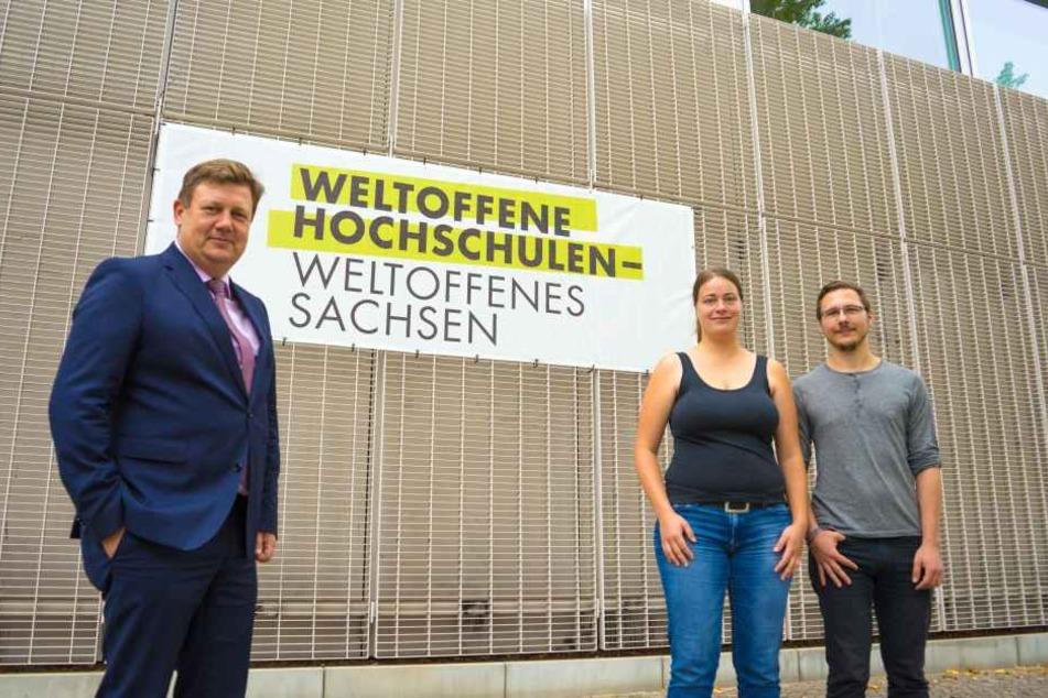 """Gemeinsam mit Prof. Markus Krabbes stehen die HTWK-Studierenden Marie Hartung und Toni Nabrotzky vor dem am Nieper-Bau platzierten Banner sinnbildlich für das Selbstverständnis der Einrichtung als """"Weltoffene Hochschule""""."""