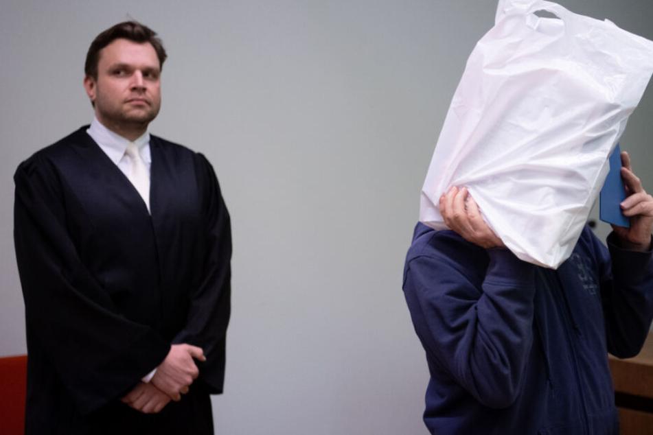 Der wegen sexuellen Missbrauchs 67-jährige Angeklagte (r) steht vor Prozessbeginn im Landgericht zusammen mit seinem Anwalt Benjamin Ruhlmann im Sitzungssaal und hält sich Plastiktüte und Ordner vors Gesicht.