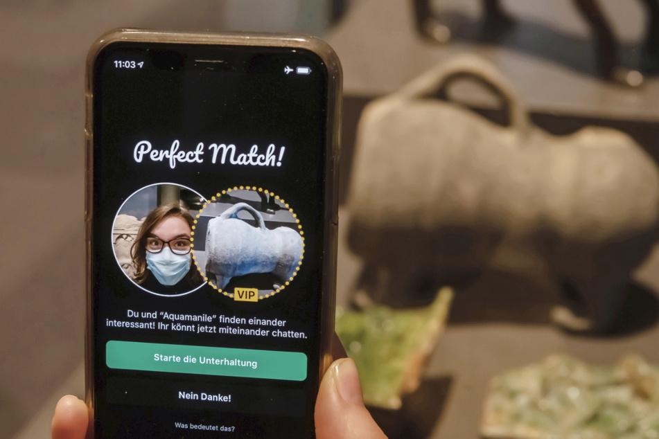 Im Badischen Landesmuseum wird vor einer Aquamanile aus dem Spätmittelalter auf einem Smartphone eine App gezeigt, mit der Museumsbesucher Kontakt zu Ausstellungsobjekten aufbauen können. Noch ist die App in der Mache.