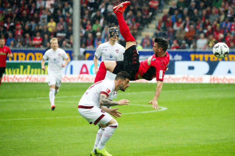 Artistisch: Marco Terrazzino (r.) hebt im Spiel des SC Freiburg gegen Nürnberg ab - Tim Leibold vom Club kann sich nur noch ducken.