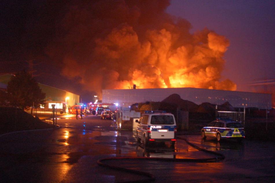 Auch am Montagabend brannten die drei Lagerhallen, in denen gepresste Plastik gelagert wird, noch lichterloh.