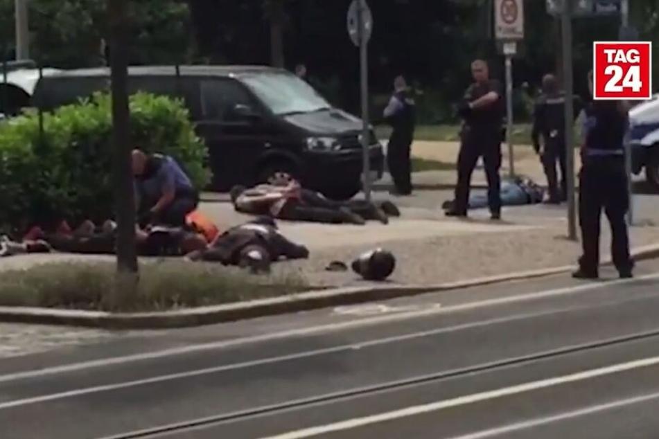 Ausschnitt aus dem Video: Der tote Rocker (re.) liegt auf der Straße, auf dem Gehweg werden andere Rocker festgenommen.