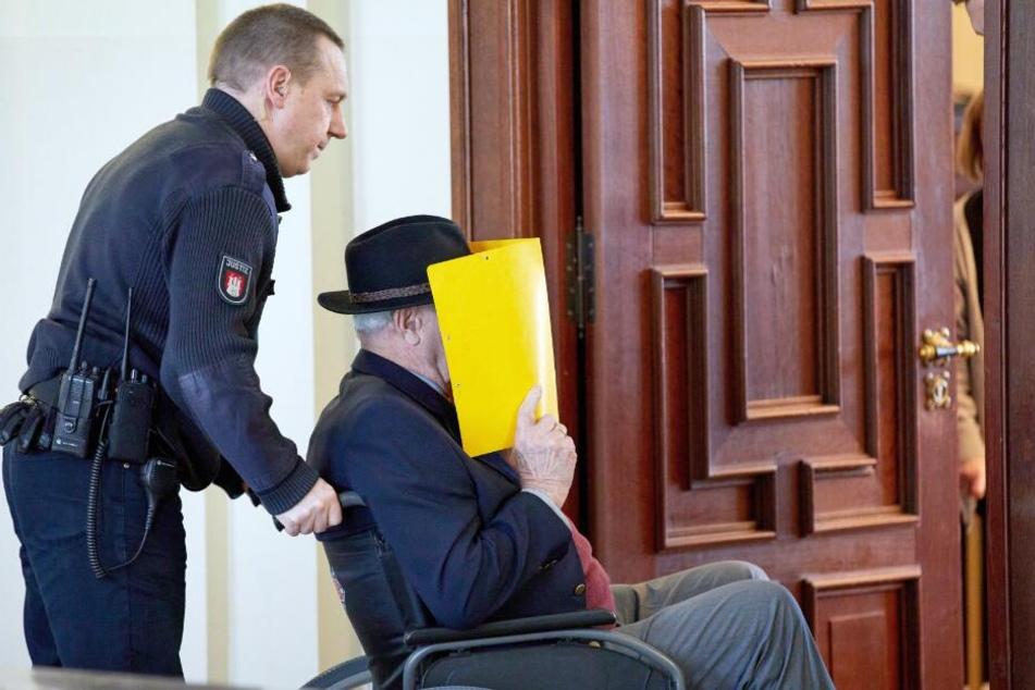 Der Angeklagte wird in einem Rollstuhl während einer Prozess-Pause aus den Gerichtssaal gebracht.