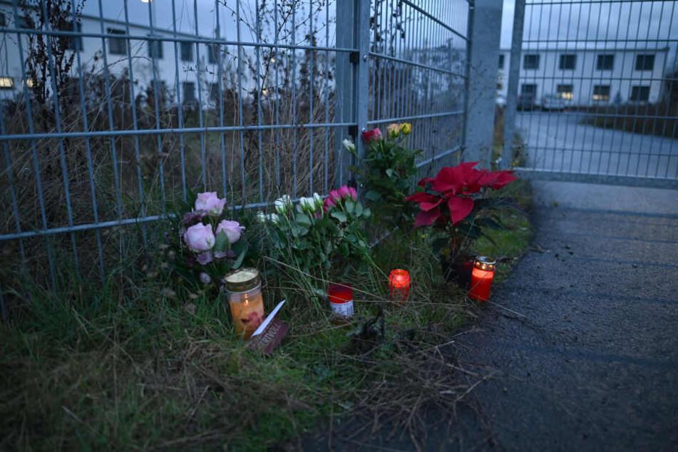 Blumen und Kerzen stehen am Eingang zu einer kommunalen Unterkunft, in der neben Flüchtlingen auch Obdachlose untergebracht sind.