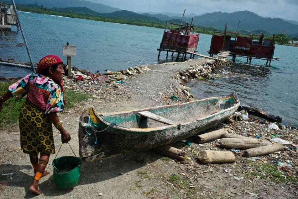 Eine ältere Frau trägt einen Eimer an der Küste des Dorfes Ustupu auf den San-Blas-Inseln. Dort leben Ureinwohner vom Stamm der Kuna.