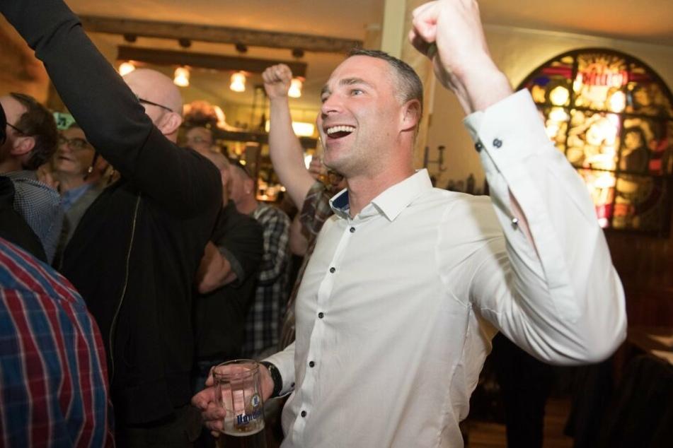 Sebastian Wippel, AfD-Landtagsabgeordneter und Oberbürgermeisterkandidat für Görlitz, jubelt während einer Wahlparty seiner Partei in einer Gaststätte.