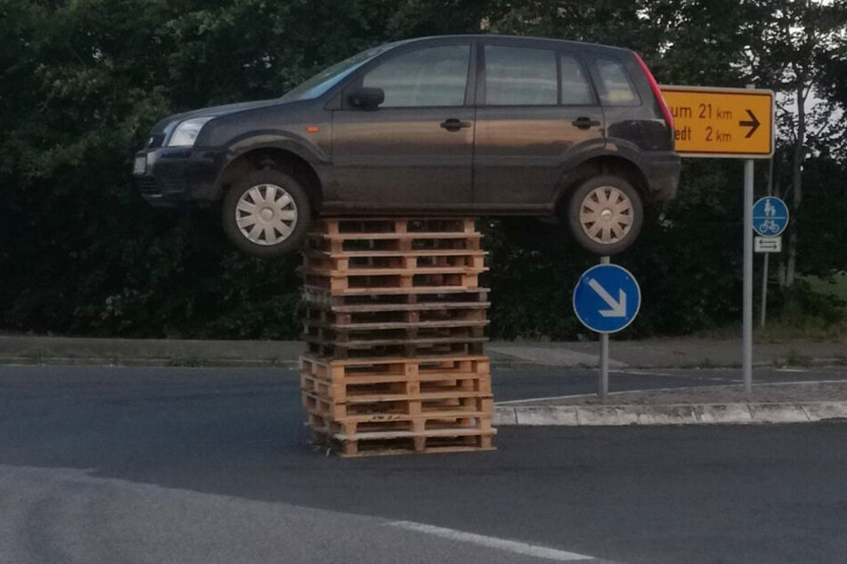 Das Auto steht auf 13 Paletten mitten auf einer Kreuzung.
