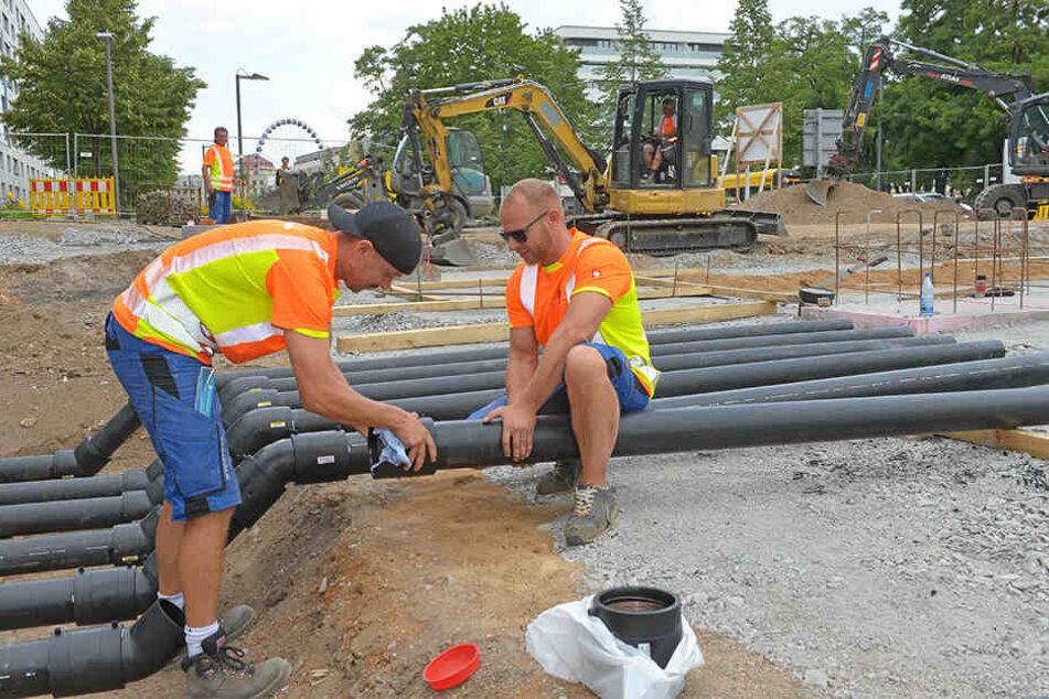Bernhard Kahnert (29, l.) und Roberto Semsch (36) verlegen eine Druckleitung für den Brunnen.