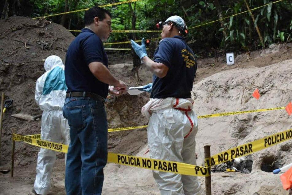 Ermittler stehen an einem Massengrab in Zentralamerika.