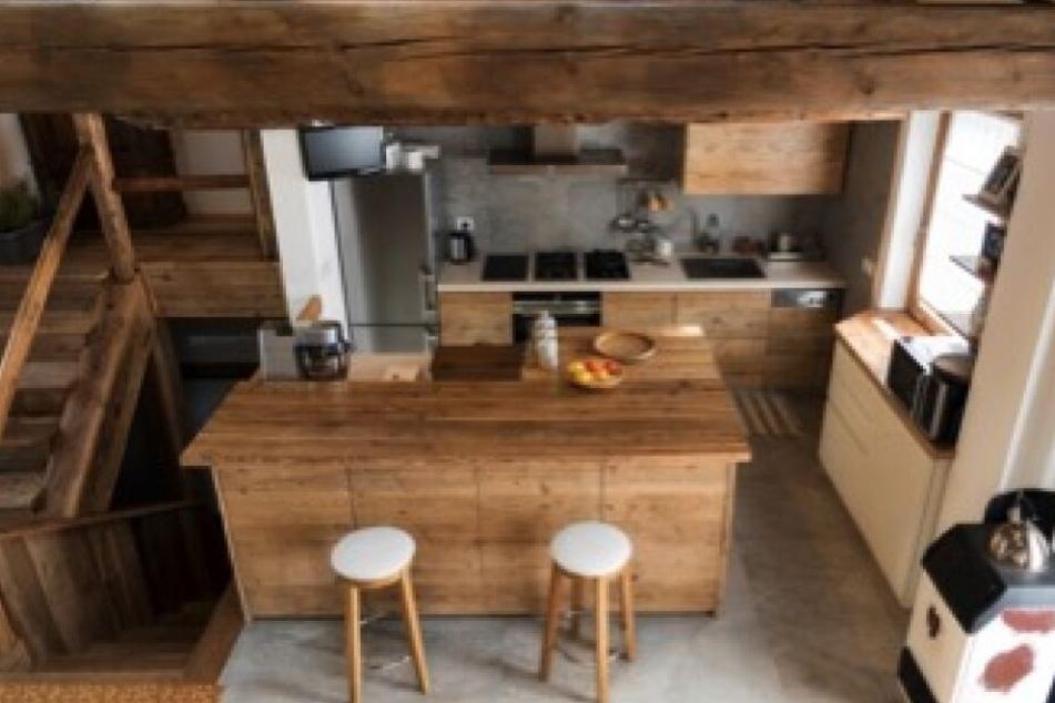 Eine offene Küche in rustikalem Stil lässt das Haus ganz anders wirken.