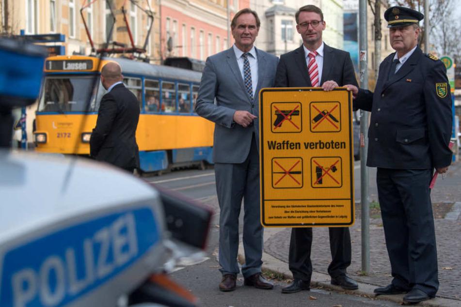 OB Burkhard Jung (SPD, v.l.), Innenminister Roland Wöller (CDU) und Polizeipräsident Bernd Merbitz zeigen auf der Eisenbahnstraße in Leipzig eines der neuen Hinweisschilder zur Waffenverbotszone.