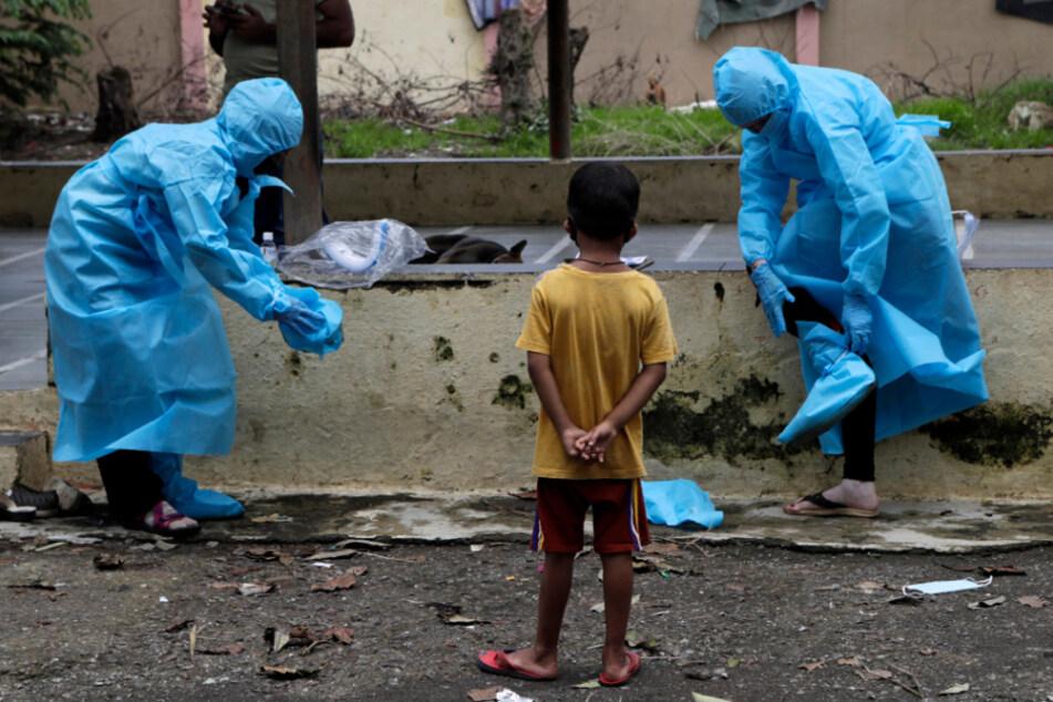 Indien, Mumbai: Mitarbeiter des Gesundheitswesens ziehen ihre Schutzbekleidung aus, nachdem sie die Anwohner eines Slums auf Covid-19-Symptome untersucht hatten.