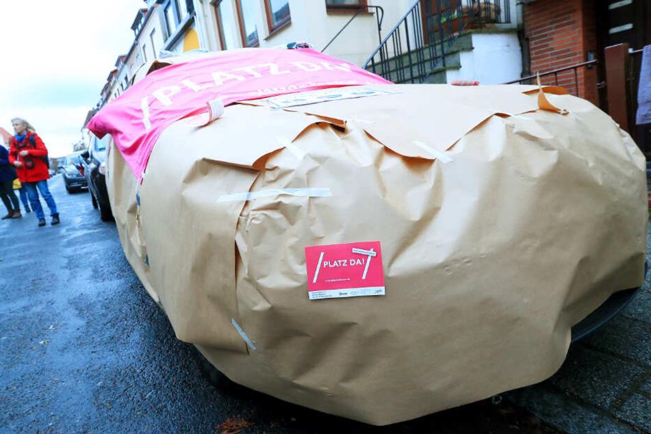 Aktivisten haben ein Auto komplett in braunes Papier eingepackt.