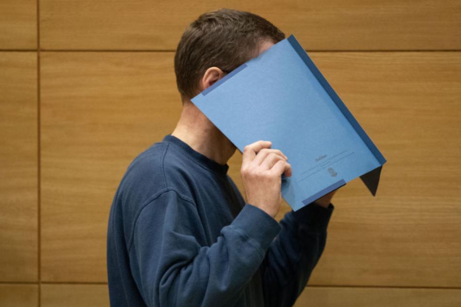 Mit einer Akte vor dem Gesicht betritt der Angeklagte den Gerichtssaal.
