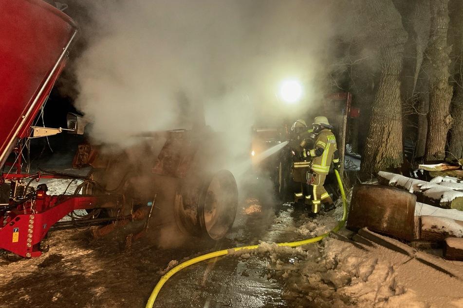 Die Einsatzkräfte der Feuerwehr Leer löschen einen brennenden Traktor.