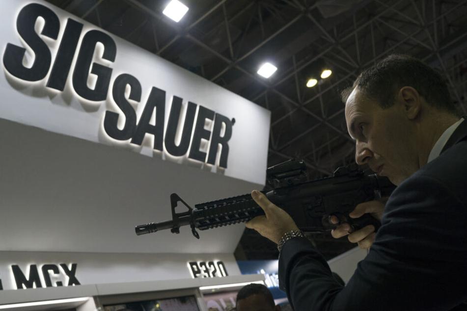 Ein Mann testet ein Sig Sauer-Gewehr, das auf der Waffenmesse LAAD Defence and Security International Exhibition in Rio De Janeiro, Brasilien ausgestellt wird.
