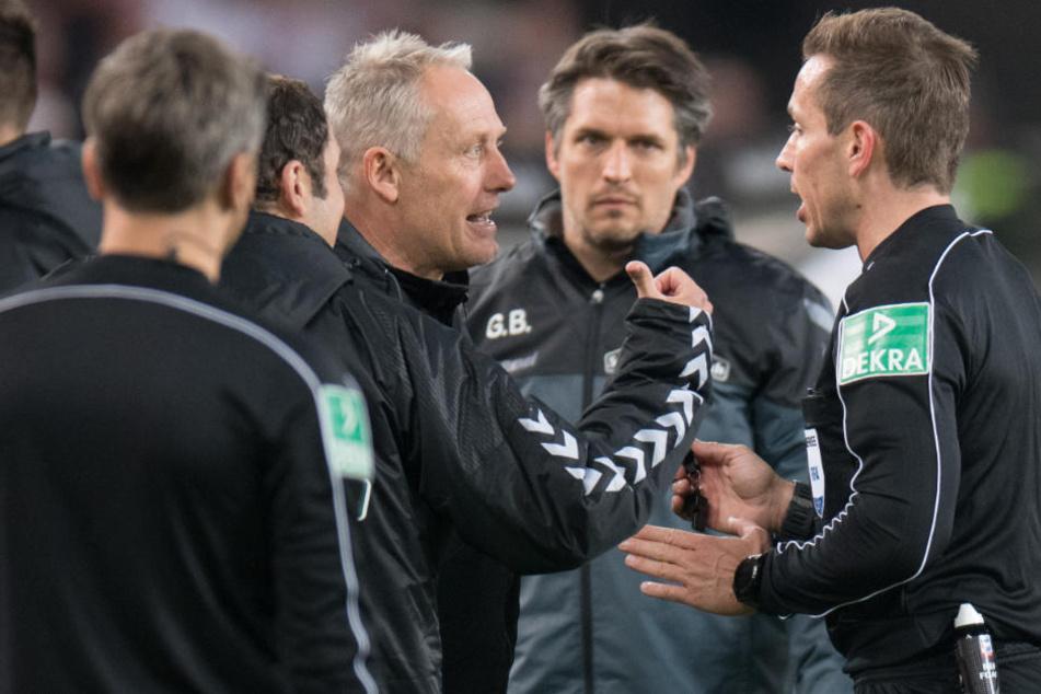 SC-Trainer Christian Streich (links) debattiert mit Schiedsrichter Tobias Stieler (rechts).