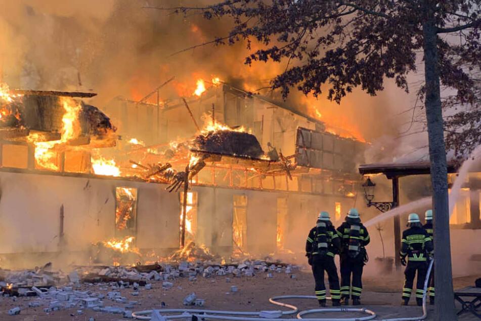 Einsatzkräfte versuchen die Flammen daran zu hindern, auf ein weiteres Gebäude überzugreifen.