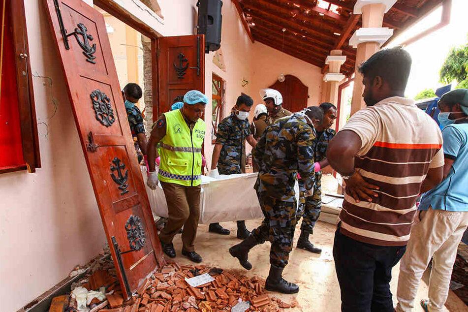 Helfer tragen nach einer Explosion am Ostersonntag in der St.-Sebastians-Kirche nördlich von Colombo den Leichnam eines Opfers aus der Kirche.