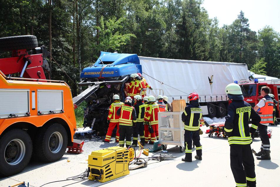 Nach einem Unfall in Thüringen untersuchen Feuerwehrleute das Fahrerhaus eines zerstörten Lkw auf der Autobahn A9.