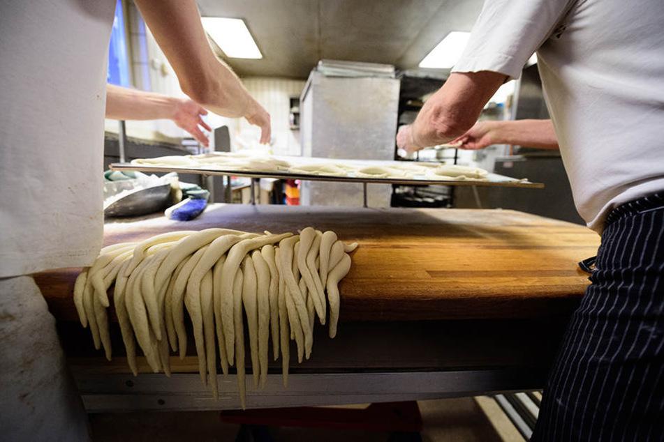 Zwei Bäcker formen schwäbische Brezeln aus Teigschnüren.