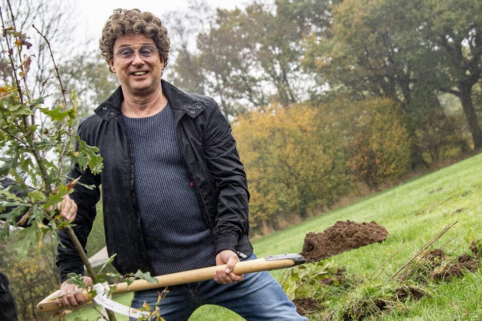 Atze Schröder steht bei der Baumpflanzung mit einem Spaten in der Hand auf einem Feld.