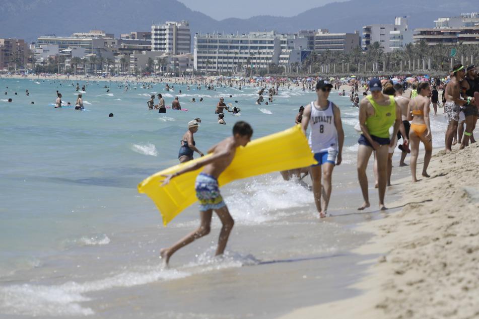 Touristen genießen die Sonne am Strand von Arenal. Wegen stark steigender Corona-Infektionszahlen stuft die Bundesregierung am Sonntag ganz Spanien und damit auch Mallorca und die Kanaren als Risikogebiet ein.