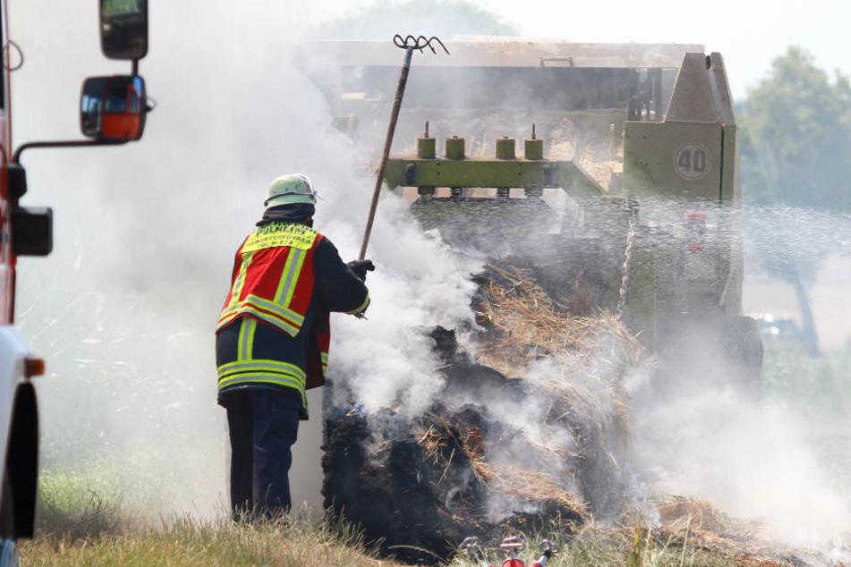 Ein Feuerwehrmann zerteilte das brennende Stroh mit einer Forke.