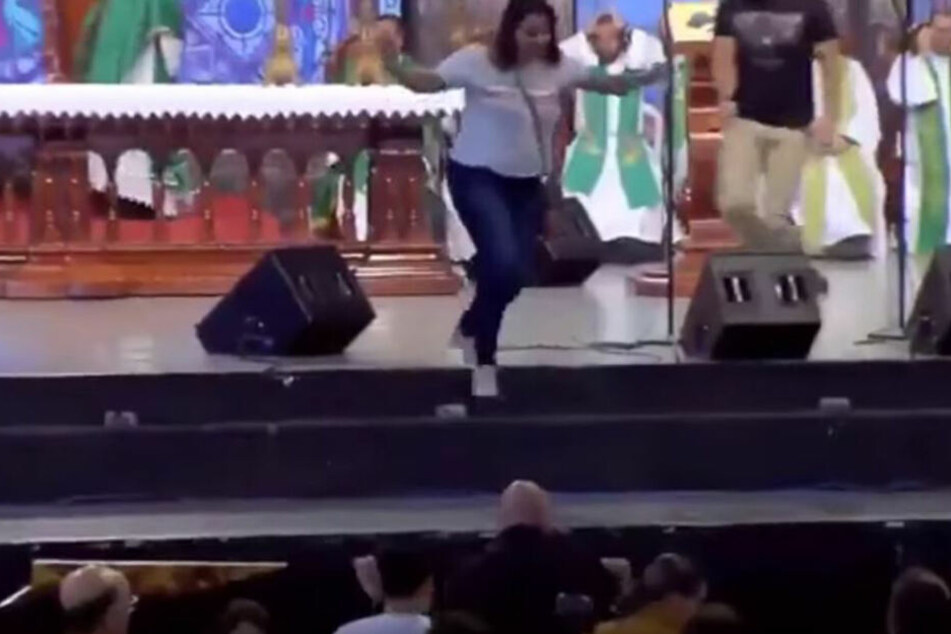 Die Frau sprang anschließend von der Bühne, von welcher der Priester kurz zuvor fiel.