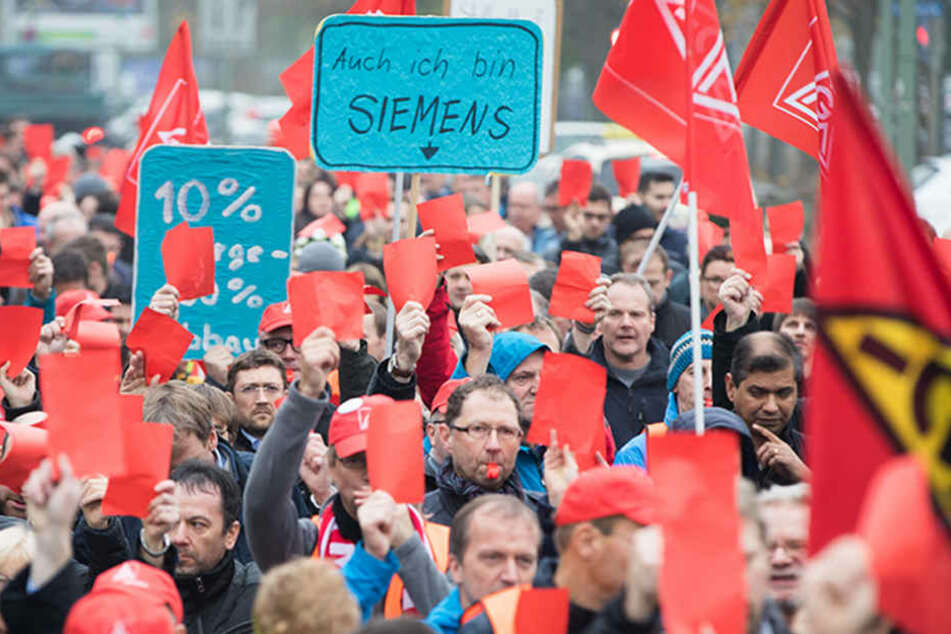 Die Rote Karte für Siemens-Chef Joe Kaeser halten in Offenbach (Hessen) Beschäftigte der Siemens-Niederlassung Offenbach gegen einen geplanten Stellenabbau in die Höhe.