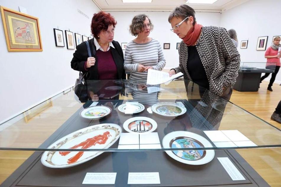 Kuratorin Brigitta Milde (r.) zeigt die von Sowjet-Künstlern  verzierten Teller der Zarenfamilie.