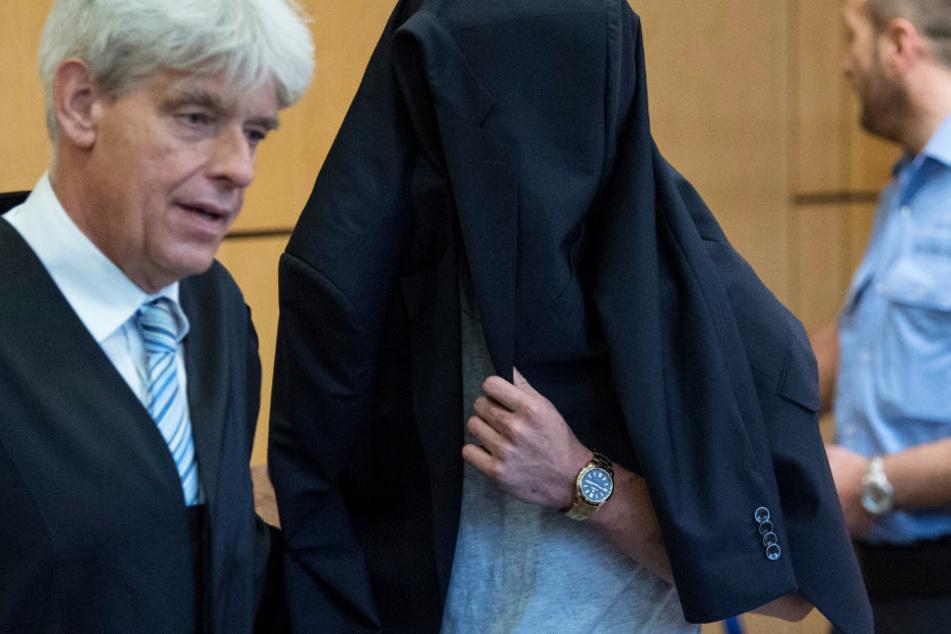 Verhüllt mit dem Jacket seines Verteidigers (l) betrat der Angeklagte den Verhandlungssaal.