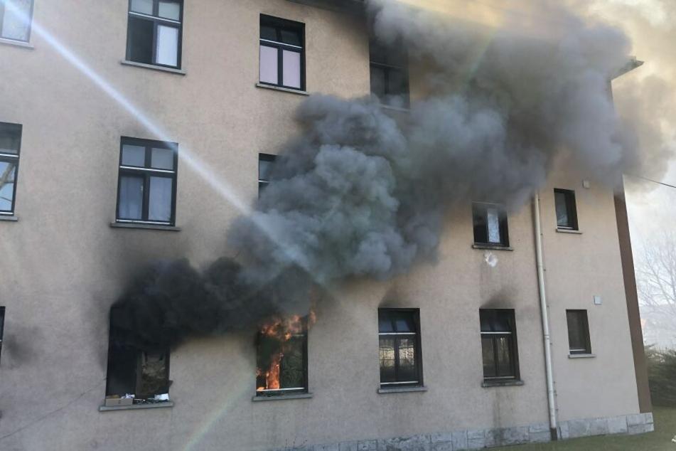 Schwarzer Rauch steigt aus einem Fenster der Unterkunft empor.