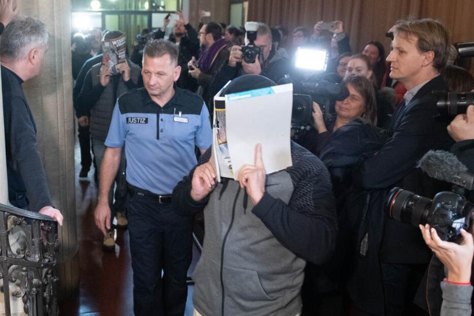 Einer von vier Angeklagten betritt beim Prozess-Beginn den Gerichtssaal.
