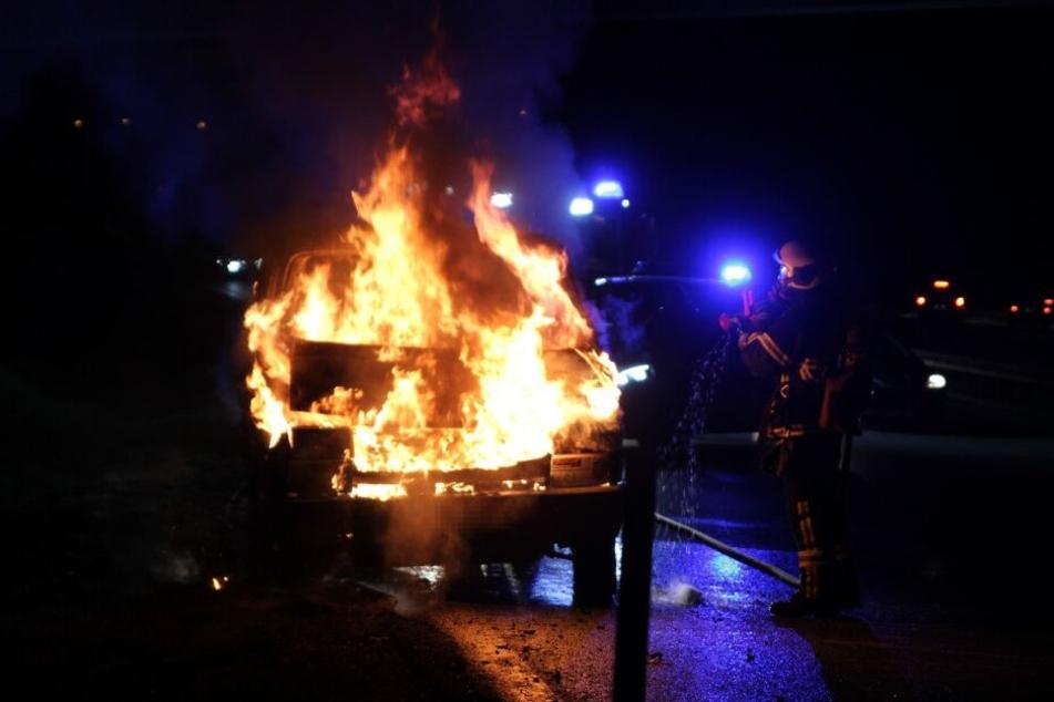 Ein Feuerwehrmann versucht den Fahrzeugbrand mit spezieller Ausrüstung einzudämmen.