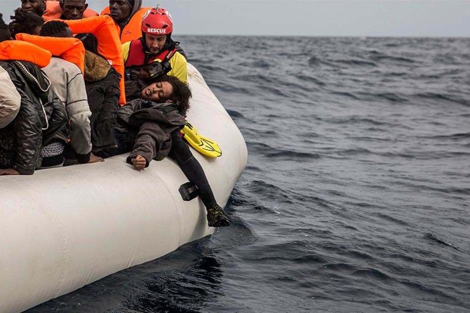 18.02.2018, Mittelmeer: Eine Frau liegt erschöpft in den Armen eines Mitarbeiters der spanischen Menschenrechtsorganisation Proactiva Open Arms auf einem überfüllten Rettungsboot nördlich von Al-Khums (Libyen).