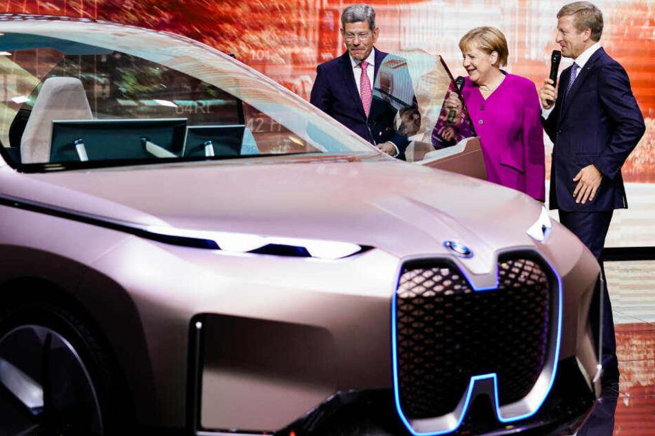 Mattes (li.) mit Bundeskanzlerin Angela Merkel (CDU) und dem Vorsitzenden des Vorstands der BMW AG am Stand von BMW bei der IAA.