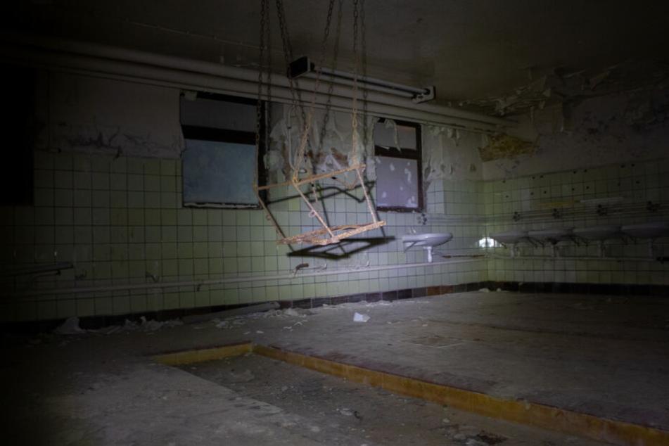 Ein großer Waschraum mit Waschbecken Duschen. In der Mitte hängt eine Schaukel von der Wand.
