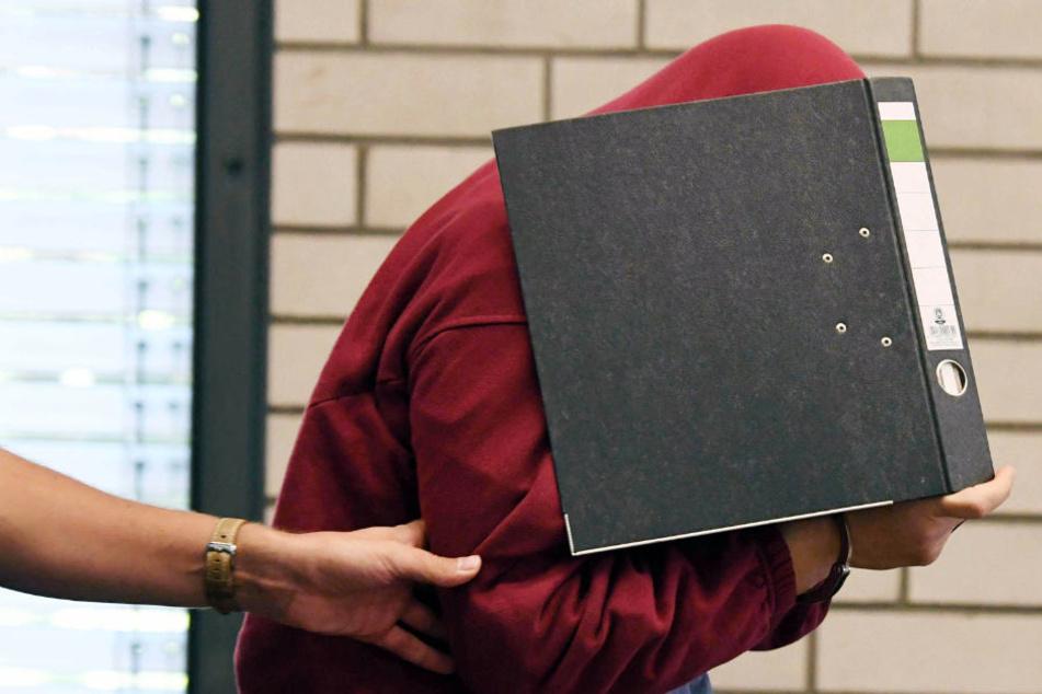 Der Angeklagte versteckt sein Gesicht hinter einem Aktenordner. (Archiv)