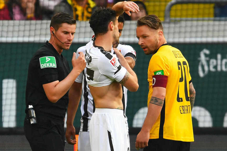 St. Paulis Jan-Philipp Kalla (m.) Shows Dynamos Patrick Ebert and referee Robert Kempter the ball print. The referee was not deterred, decided on hand penalty!