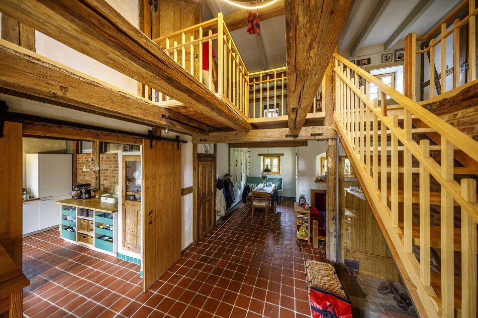 Der offene Flur- und Wohnbereich lädt zum Verweilen ein. Innen dominiert eine Mischung aus altem und neuem Holz.