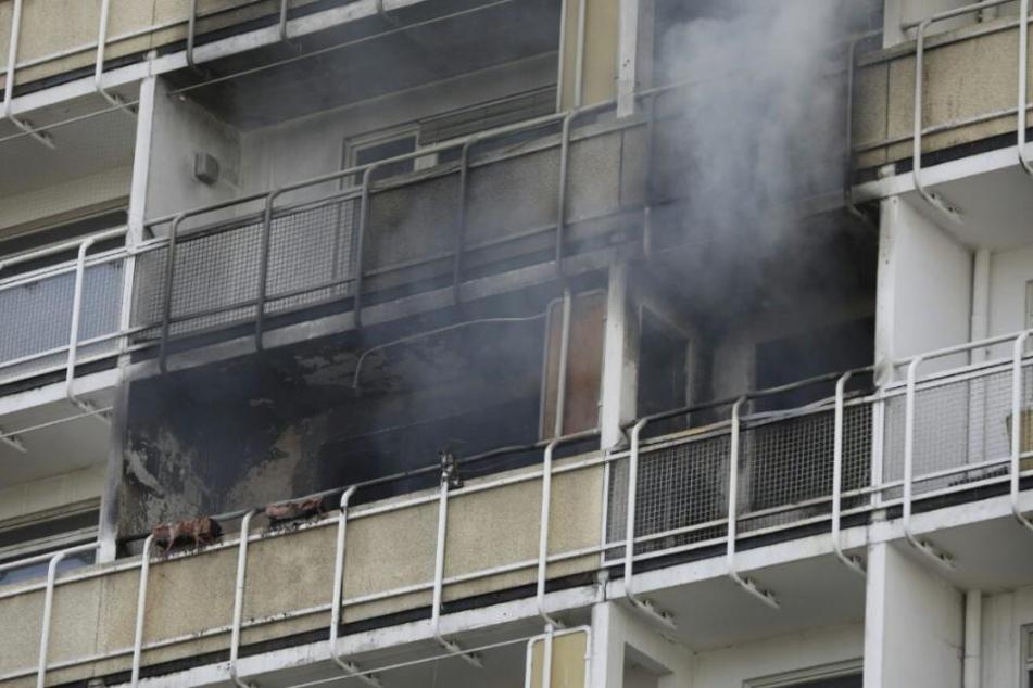 Der Balkon ist völlig verkohlt, aus der Brandwohnung quillt noch Rauch.