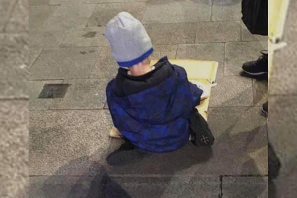 Obdachloser Junge (5) isst Nudeln von Pappkarton