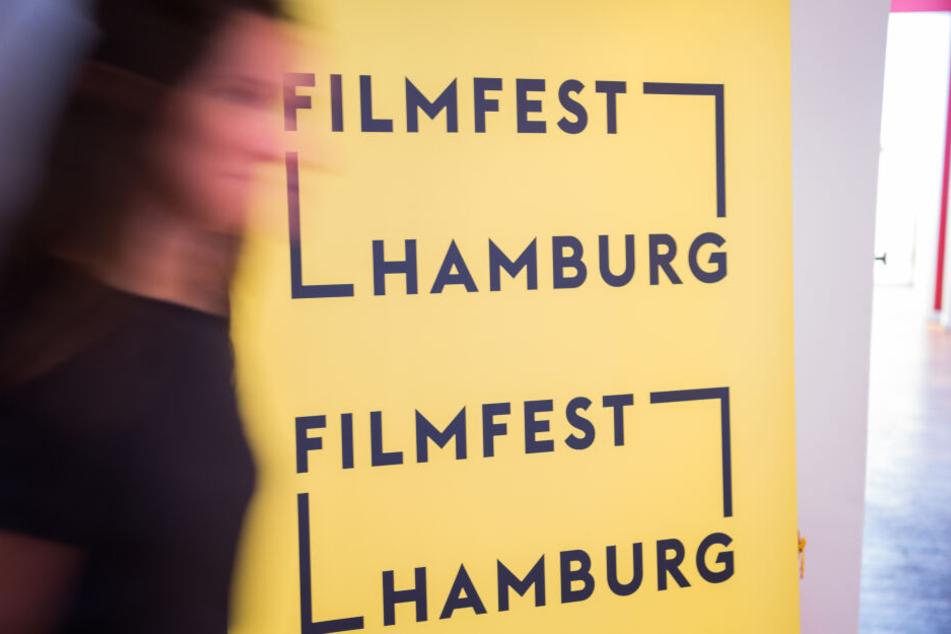 Eine Frau läuft an einem Aufsteller des Filmfests Hamburg vorbei.