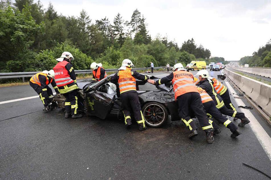Die Kameraden der Feuerwehr schieben den demolierten Porsche von der Fahrbahn.