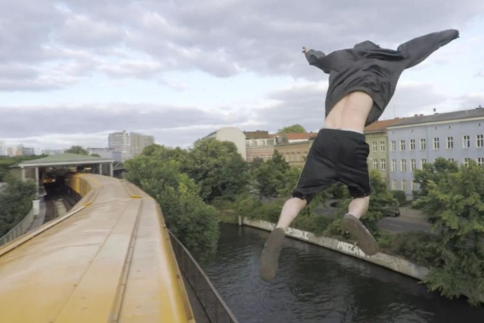 Ein Mann springt während der Fahrt vom Dach eines Zuges in den angrenzenden Landwehrkanal.