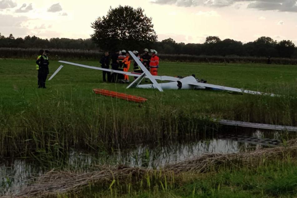 Einsatzkräfte stehen neben dem abgestürzten Segelflieger.