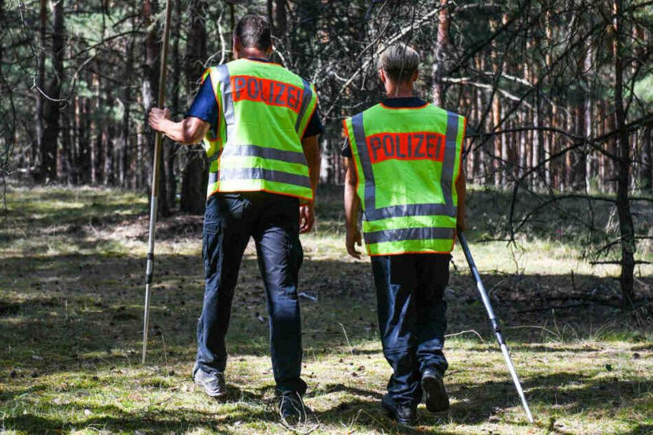 Zwei Polizisten suchen in einem Waldstück nach der vermissten Rebecca.