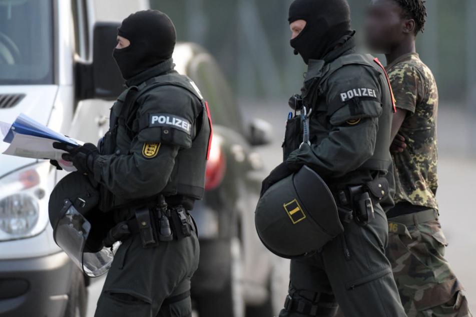 In der Landeserstaufnahmeeinrichtung für Flüchtlinge (LEA) in Ellwangen wird ein Mann von maskierten Polizisten eskortiert. (Archivbild)
