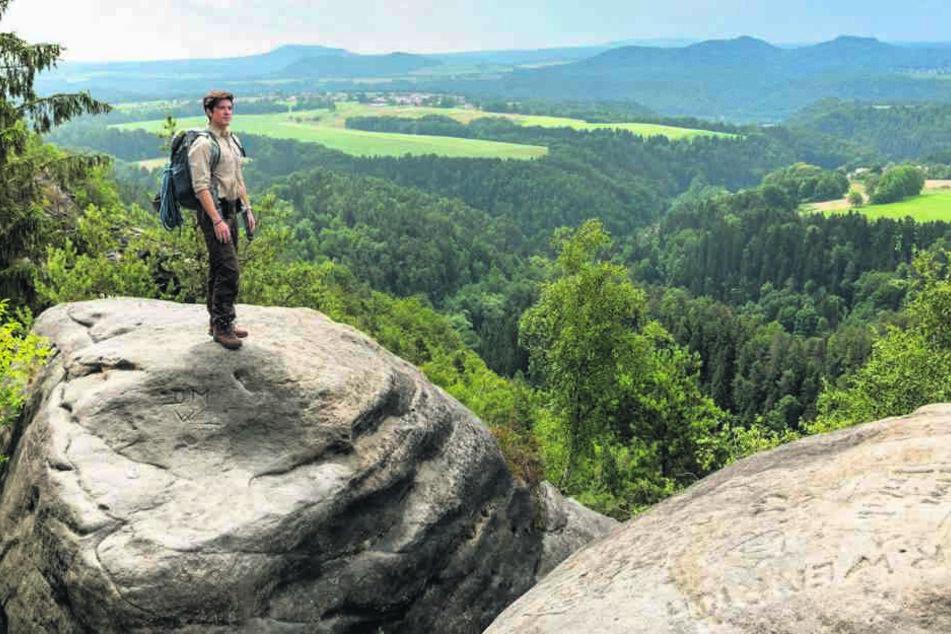 Ranger Jonas (Philipp Danne) lässt hoch oben auf dem Fels den Blick über die herrliche Landschaft schweifen.